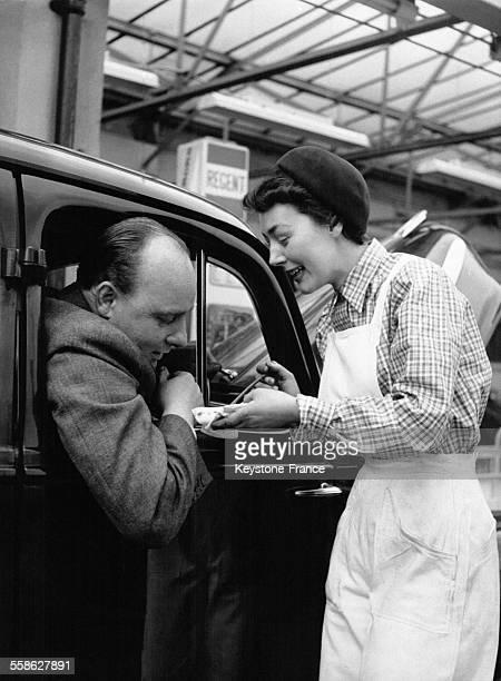 Jeune femme mécanicienne montrant au client la fuite de la jauge de sa voiture