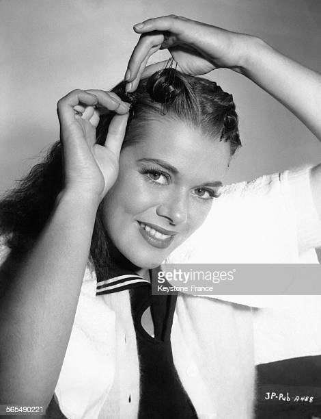 Jeune femme mettant une épingle à cheveux dans sa coiffure circa 1948