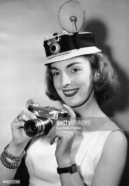 Jeune femme portant un appareil photo chapeau et tenant un Periflex 3 appareil de fabrication anglaise à l'occasion de l'ouverture du salon de la...
