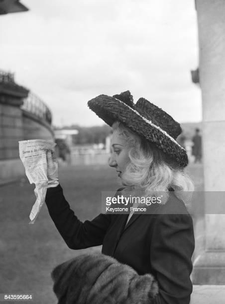 Jeune femme portant un chapeau de paille à Longchamp à Paris France en 1946