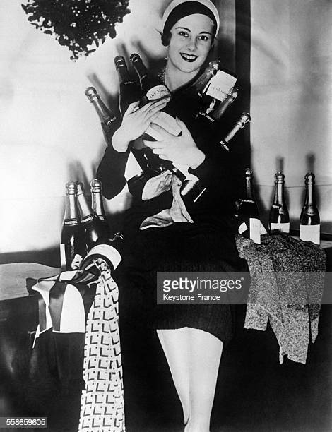Jeune femme tenant des bouteilles de champagne qui contiennent des cravates bijoux et autre cadeaux idée de cadeaux de Noël d'un grand magasin...