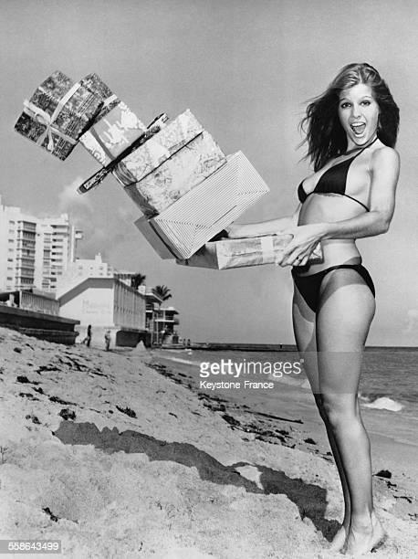 Jeune fille sur une plage avec des cadeaux pour annoncer le debut des courses de Noel a Miami Floride