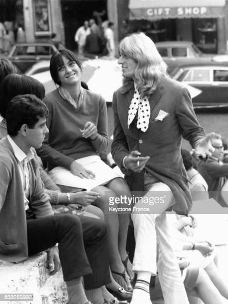 Jeune homme avec des cheveux longs discutant avec un groupe d'amis place d'Espagne à Rome Italie le 21 septembre 1967