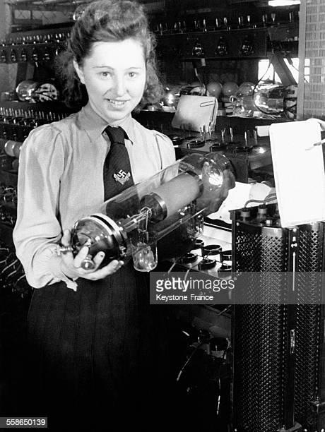 Jeune Volontaire Allemande tenant une lampe dans une usine de prouction visant à participer à l'effort de guerre en Allemagne en 1943