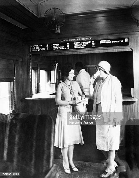 Jeunes femmes accoudées au comptoir du premier bar installé dans un train celuici assurant la liaison New YorkWashington aux EtatsUnis circa 1930