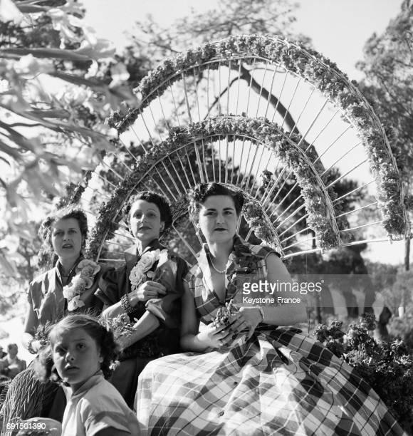 Jeunes filles assises sur des chars fleuris défilent dans les rues de JuanlesPins France le 7 avril 1953