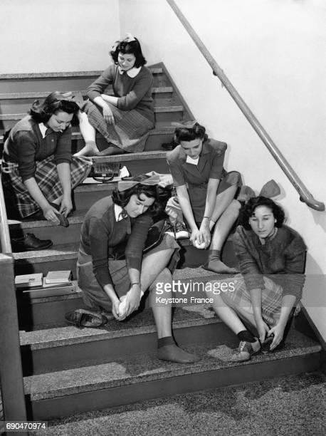 Jeunes filles assises sur les marches de l'escalier se massent les pieds douloureux car elles n'ont pas le droit de prendre l'ascenseur