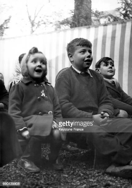 Jeunes spectateurs regardant le Guignol des Buttes Chaumont à Paris France le 28 février 1940