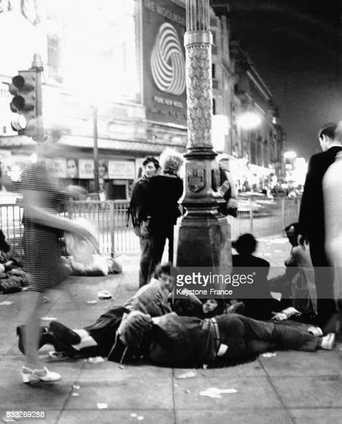Jeunes squatteurs dormant autour d'un lampadaire sur Piccadilly Circus à Londres RoyaumeUni circa 1960