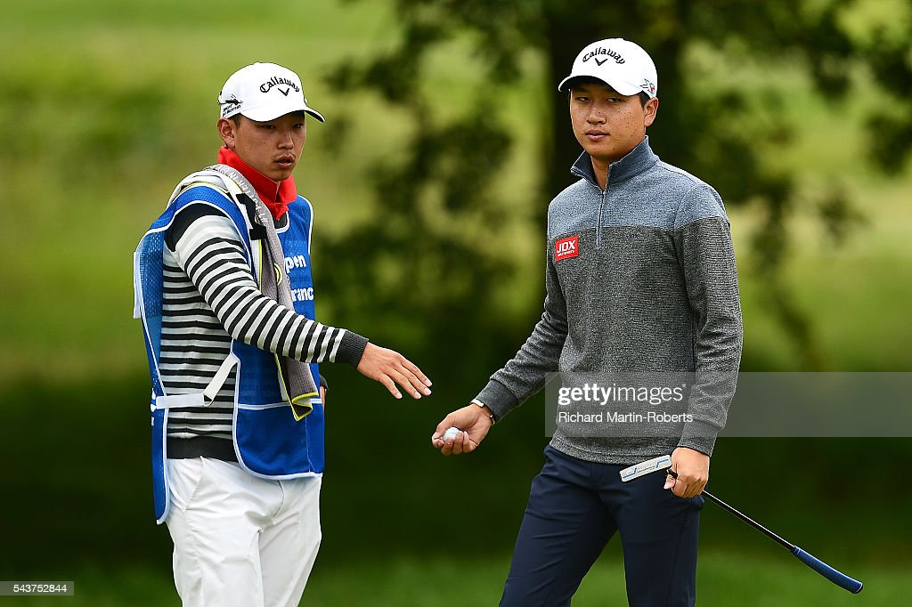 Jeunghun Wang of Korea hands his ball to his caddie on the 14th green during the first round of the 100th Open de France at Le Golf National on June 30, 2016 in Paris, France.