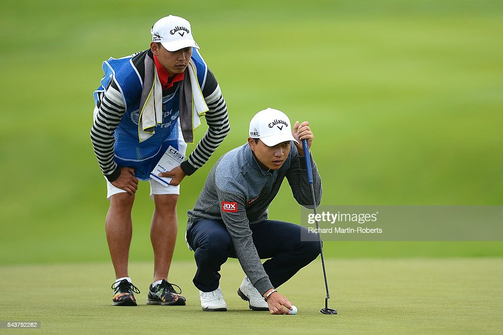 Jeunghun Wang of Korea lines up a putt with his caddie on the 13th green during the first round of the 100th Open de France at Le Golf National on June 30, 2016 in Paris, France.