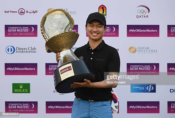 Jeunghun Wang of South Korea poses with the trophy following his victory in the playoff during the fourth round of the Commercial Bank Qatar Masters...
