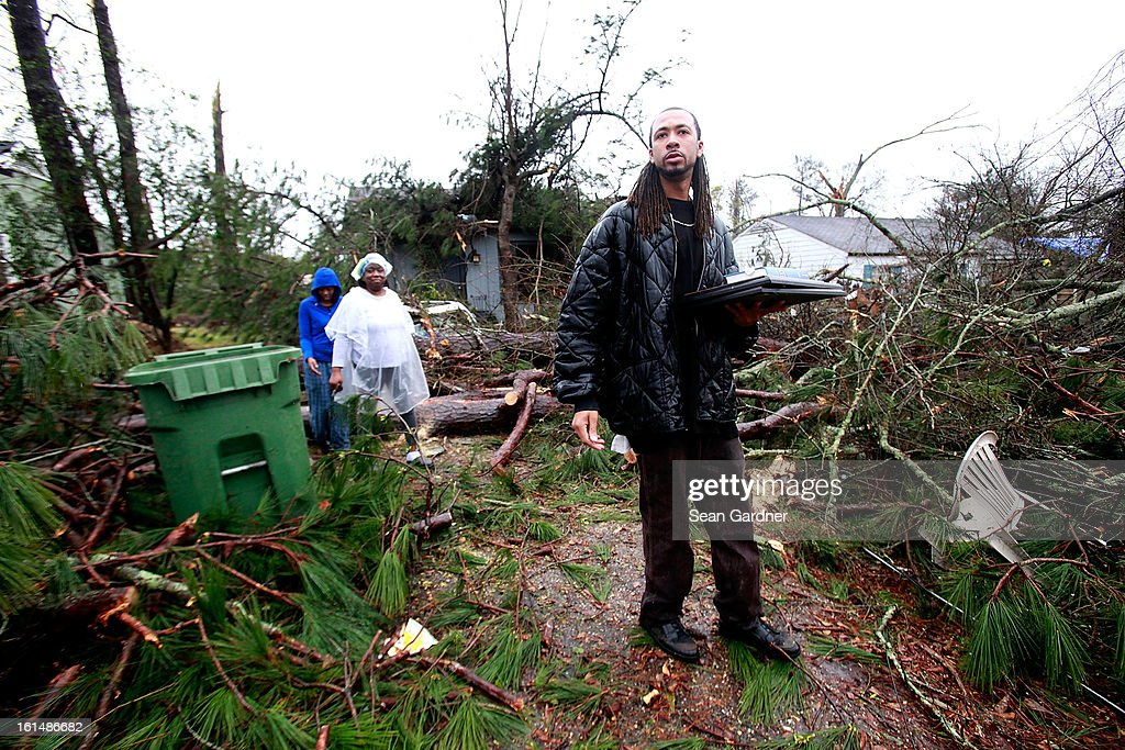 Jevern Gillispie (R) helps bring out belongings form Lisa Hill and Elunion Cooper's home after a tornado touched down yesterday evening February 11, 2013 in Hattiesburg, Mississippi. Hundreds of homes were destroyed and over sixty people injured when the tornado ripped through the town.