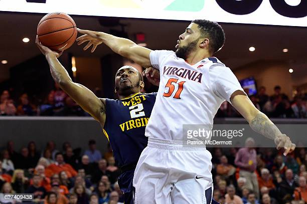 Jevon Carter of the West Virginia Mountaineers and Darius Thompson of the Virginia Cavaliers battle for a rebound in the first half during a game at...