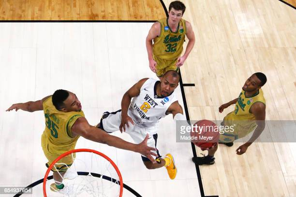 Jevon Carter of the West Virginia Mountaineers takes a shot against Bonzie Colson of the Notre Dame Fighting Irish during the second round of the...