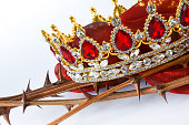 Close-up view of a beautiful crown with red jewels on thorny twigs with red cloth symbols from Christanity Good Friday