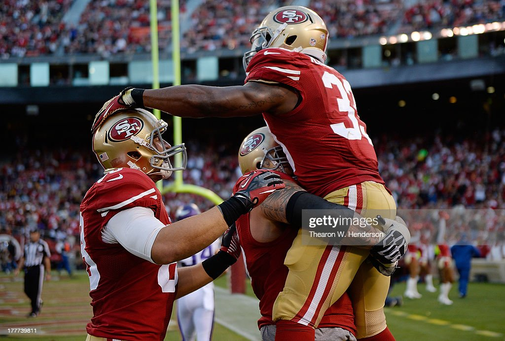 Jewel Hampton #33 of the San Francisco 49ers celebrates with Adam Snyder #68 and Garrett Celek #88 after Hampton scored on a three yard touchdown run in the fourth quarter against the Minnesota Vikings at Candlestick Park on August 25, 2013 in San Francisco, California. The 49ers won the game 34-14.