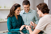 Jeweler assisting couple with rings