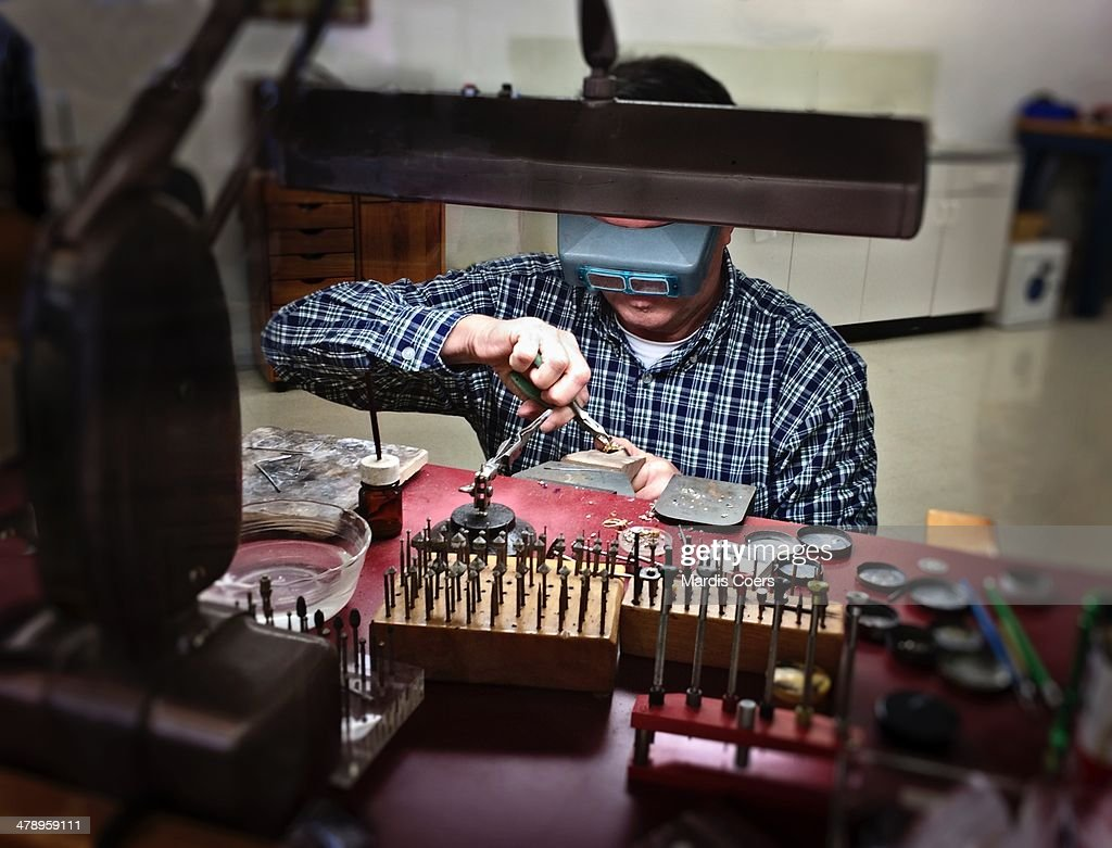 Jeweler at his workbench and wearing a headband magnifying glass, California.