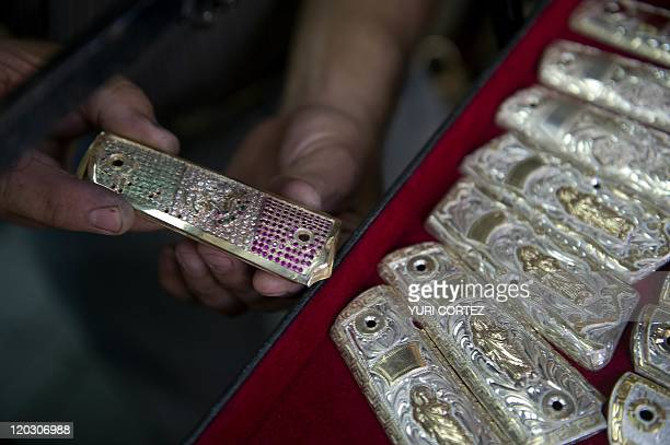 A jeweler shows a gun butt made of gold diamonds emeralds and rubies to form the Mexican flag in Culiacan Sinaloa state on July 12 2011 The...