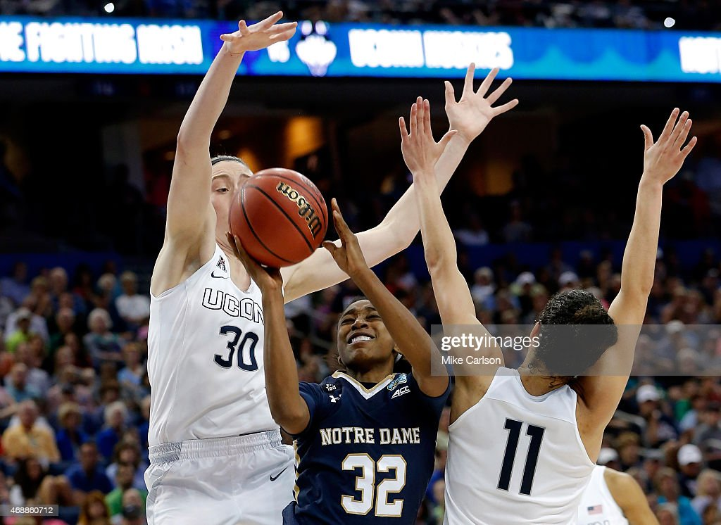 Jewell Loyd of the Notre Dame Fighting Irish goes up for a basket as Breanna Stewart and Kia Nurse of the Connecticut Huskies defend during the NCAA...