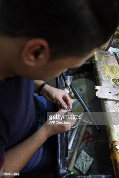 A jeweller fabricates a ring in a workshop in the main market of Iraq's holy city of Najaf on September 13 2017 Strategically located facing the...