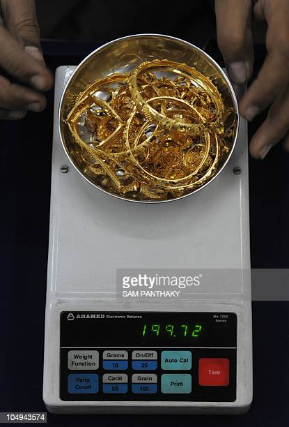 A jeweller weighs gold jewellery at a shop in Ahmedabad on October 7 2010 Gold surged to a record 135650 USD an ounce in Hong Kong trade Dealers are...