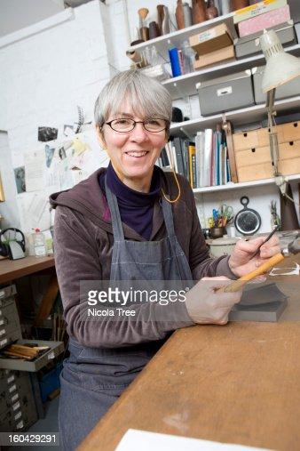 A Jeweller working in her studio : Stock Photo