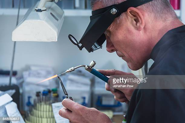 Jewellery craftsman using miniature blowtorch on platinum ring