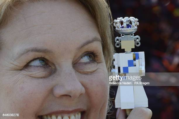 Jewellery designer Dinny Hall poses with a new 10cm high LEGO model of Queen Elizabeth II complete with a real diamond encrusted crown is unveiled at...