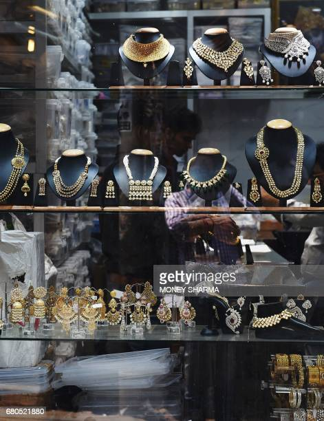 Jewellery is displayed for sale in shop windows in the Indian capital New Delhi on May 8 2017 Fat wads of bank notes move across counters in Old...