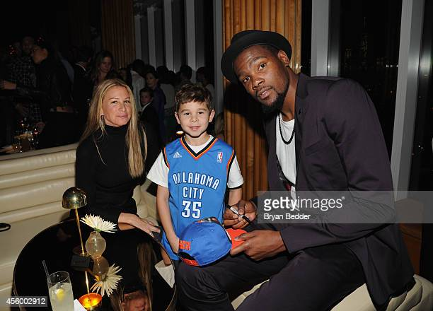 Jewelry designer Jennifer Fisher and son pose for a photo with NBA player Kevin Durant as they attend NBA 2K15 Launch Celebration at The Standard on...