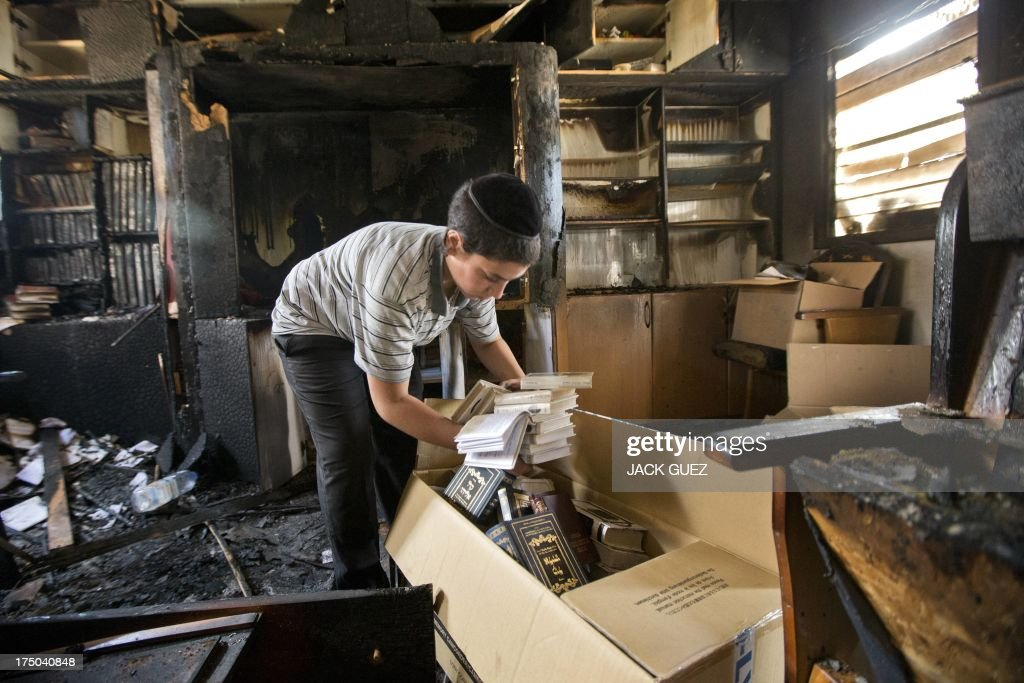 A Jewish boy collects religious books following an overnight fire at a synagogue in the Israeli coastal city of Netanya on July 30, 2013. It is not know how or why the fire started.