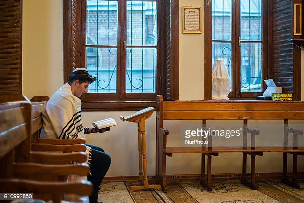 A Jewish boy in the traditional garment reads words of Torah during the Mincha prayer service in the Sixdomed Synagogue in Qrmz Qsb or Red Town Quba...