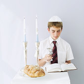Jewish boy reading the talmud with a Kiddush cup in hand