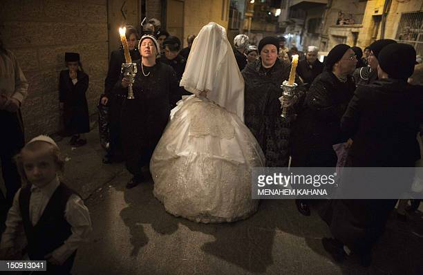 A Jewish bride from the UltraOrthodox Tholdot Avraham Yizhak Hasidic group is escorted by her family members to her wedding ceremony in the Ultra...