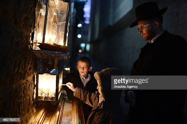 Jewish children and an ultra orthodox Jewish man light candles on the seventh night of the Jewish festival of Hanukkah in the Old City of Jerusalem...