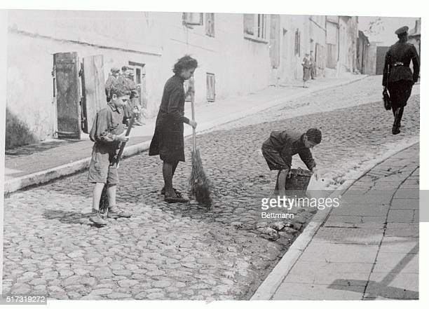 Jewish children in the German created ghetto of Warsaw clean a street as a hygienic measure against the ever present danger of epidemics The boy at...