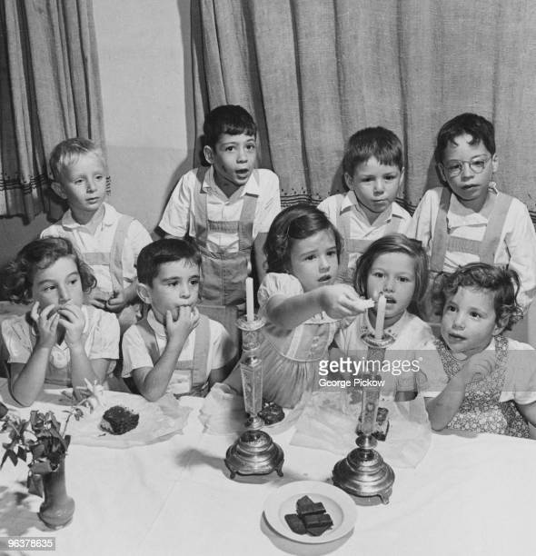Jewish children lighting the two Shabbat candles on a friday in Israel circa 1955