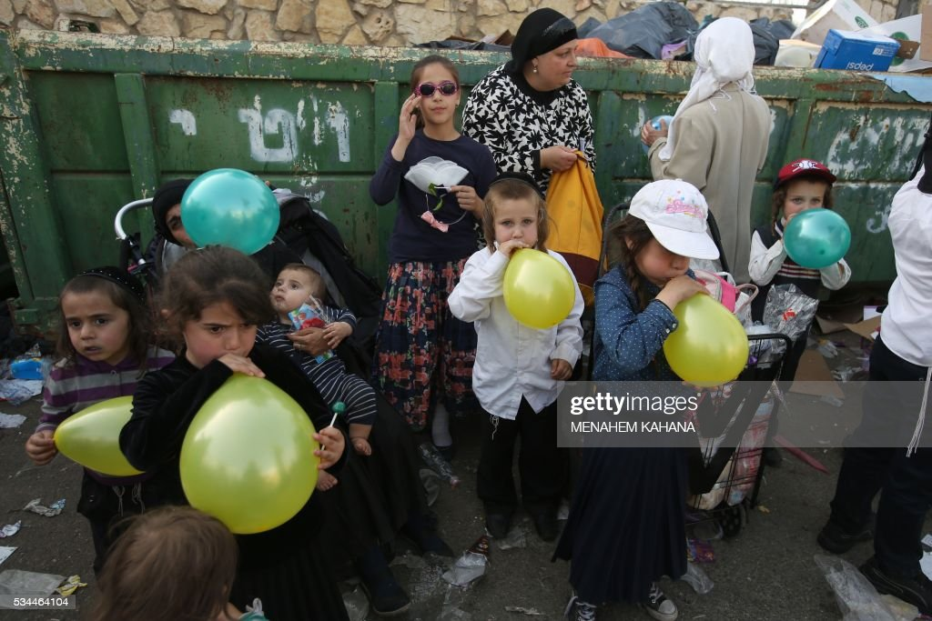 Jewish children play with balloons near the grave site of Rabbi Shimon Bar Yochai in the northern Israeli village of Meron, on May 26 2016, at the start of the day-long holiday of Lag Baomer that commemorates the Jewish scholar's death. Thousands of religious Jews light large bonfires all night long and visit the shrine of Bar Yochai, one of the most prominent sages in Jewish history, during the holiday. KAHANA