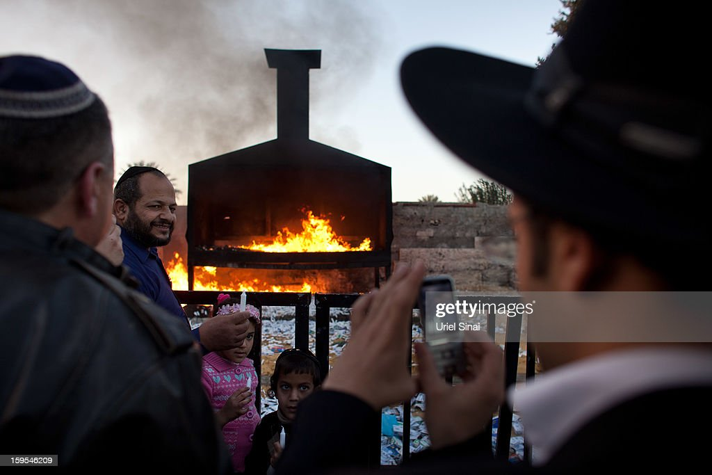 A Jewish family get their picture taken next to a burning pyre at the grave of Rabbi Yisrael Abuhatzera, known as the sage Baba Sali, on January 15, 2013 in the southern Israeli town of Netivot, Israel. Thousands of Jews, mainly of Moroccan origin, gathered to pray and hold festivities at the tomb of the respected rabbi who was known as a miracle maker by religious Jews.