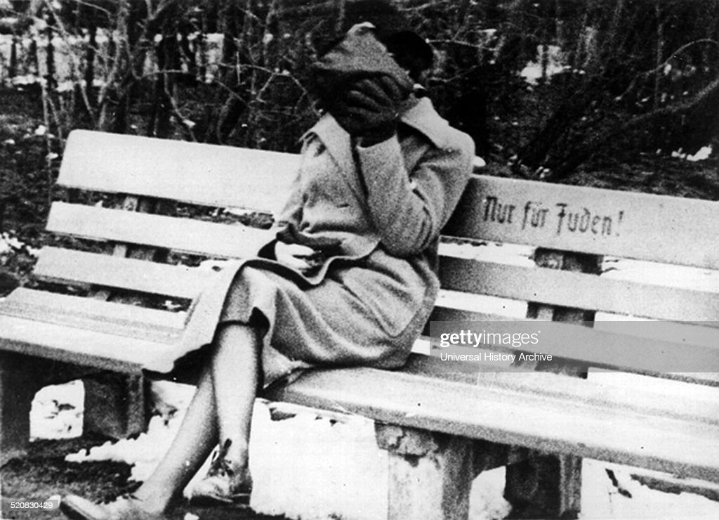A Jewish female hides her face from people as she sits on a Jew only bench Anti semitic segregation was implemented in Germany when the Nazi party...