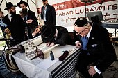 A jewish guets watches as a scribe pens the final letters on a newly dedicated Torah scroll in the Chabad Synagogue on May 7 2015 in Berlin Germany...
