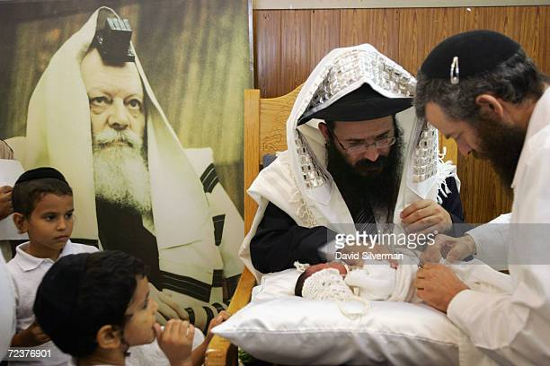 Jewish infant Or Chaim Nagar eightdaysold is ritually circumcised alongside a poster of the late Lubavicher Rabbi Schneerson in a ceremony November 2...
