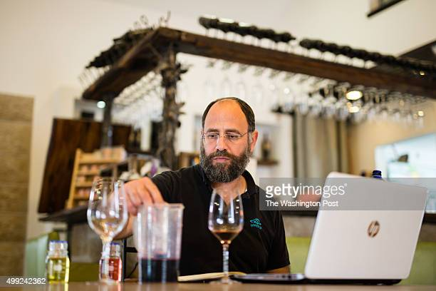 Jewish Israeli winemaker Yaacov Oryah is seen as he checks acidity levels after Malolactic fermentation at Psagot Winery on November 17 in the West...