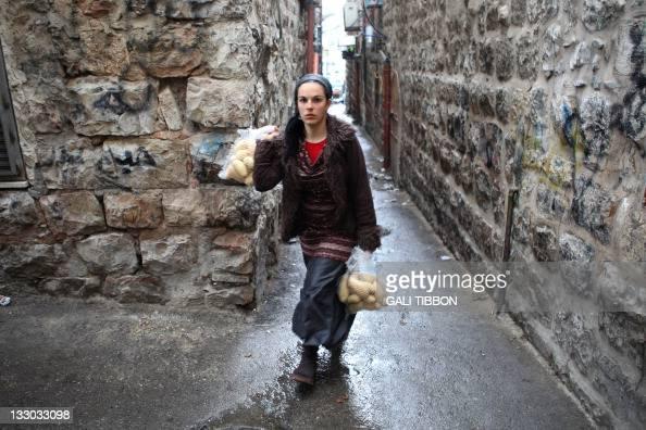 Jewish Israeli woman carries her shopping as she walks in the alley ways of the Arab part of the Jerusalem Musrara neighborhood on November 16 2011...