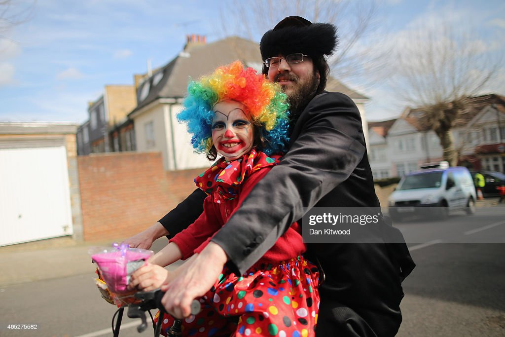 Jewish man and a young girl dresses as a clown cycle through the streets during the Jewish holiday of Purim on March 5 2015 in London England The...