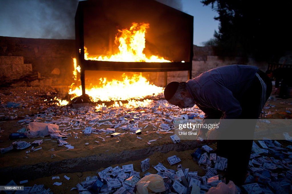 Jewish man collects candles next to a burning pyre at the grave of Rabbi Yisrael Abuhatzera, known as the sage Baba Sali, on January 15, 2013 in the southern Israeli town of Netivot, Israel. Thousands of Jews, mainly of Moroccan origin, gathered to pray and hold festivities at the tomb of the respected rabbi who was known as a miracle maker by religious Jews.