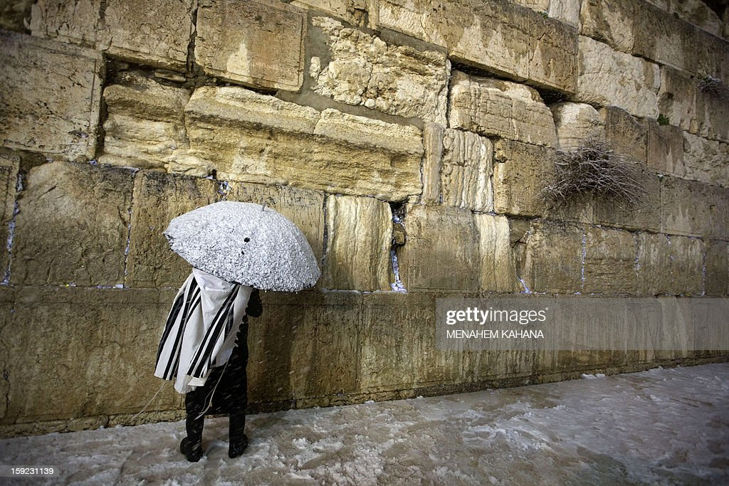 A Jewish man holding a snow-covered umbrella prays at the Western Wall in the old city of Jerusalem on January 10, 2013. Jerusalem was transformed into a winter wonderland after heavy overnight snowfall turned the Holy City and much of the region white, bringing hordes of excited children onto the streets.