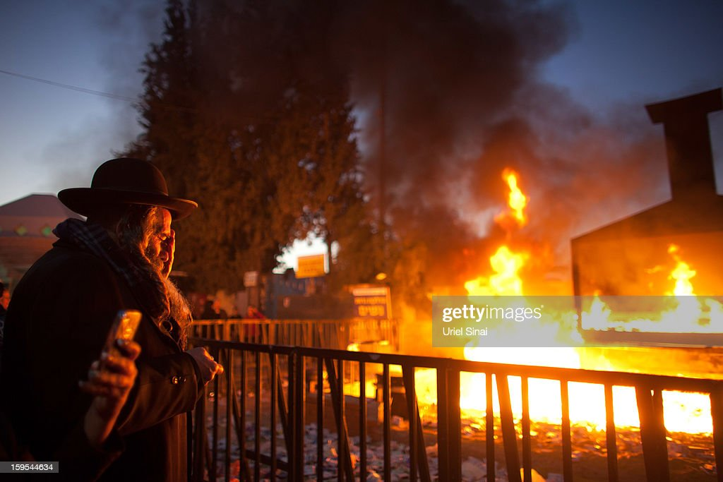 A Jewish man prays alongside a burning pyre of votive candles at the grave of Rabbi Yisrael Abuhatzera, known as the sage Baba Sali, on January 15, 2013 in the southern Israeli town of Netivot, Israel. Thousands of Jews, mainly of Moroccan origin, gathered to pray and hold festivities at the tomb of the respected rabbi who was known as a miracle maker by religious Jews.